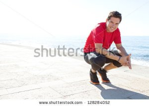 stock-photo-portrait-of-a-sports-man-crouching-down-on-a-track-by-the-sea-on-a-sunny-day-smiling-against-a-128284052